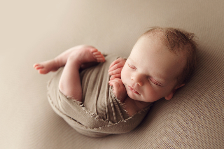 newborn baby boy curled up on a brown blanket